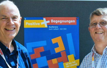 Georg Roth und Sigmar Fischer, beide Vorstände der Bundesinteressenvertretung schwuler Senioren, vor dem Veranstaltungsplakate der Positiven Begegnung.