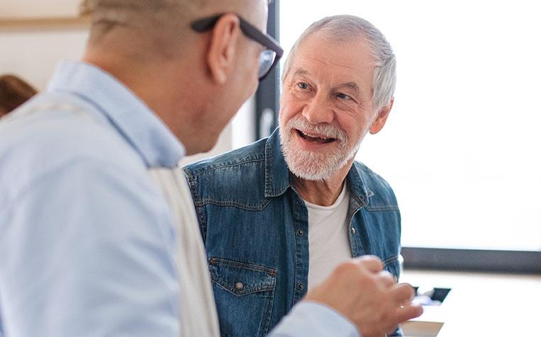 Zwei Rentner unterhalten sich. freundliche Atmosphäre. Im Hintergrund ein helles Fenster.